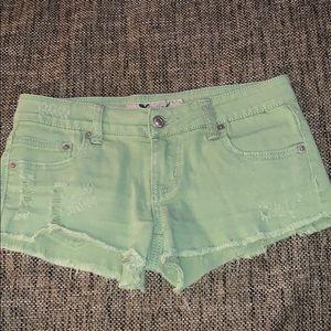 Distressed light green denim shorts